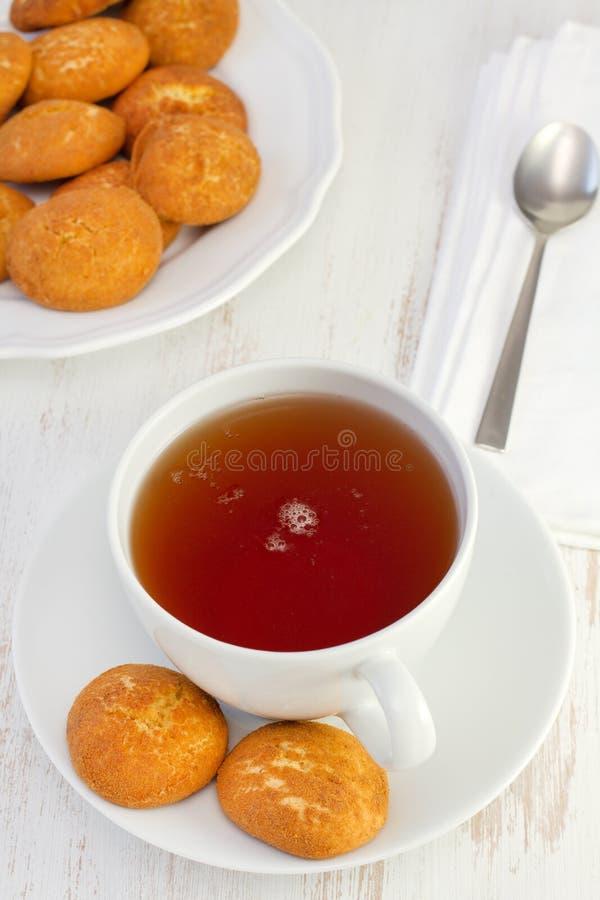 Kupa av tea med kanelbruna kakor arkivbild
