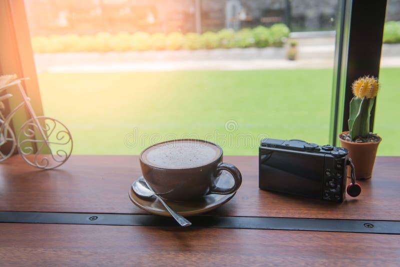 Kupa kaffe och kameran på trätabellen i coffee shop på morgonen arkivbilder