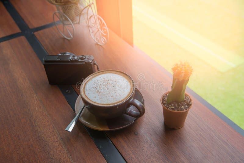Kupa kaffe och kameran på trätabellen i coffee shop på morgonen royaltyfri fotografi