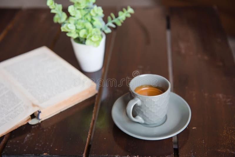 Kupa kaffe på den vita trätabellen och den gamla boken och krukan arkivbilder