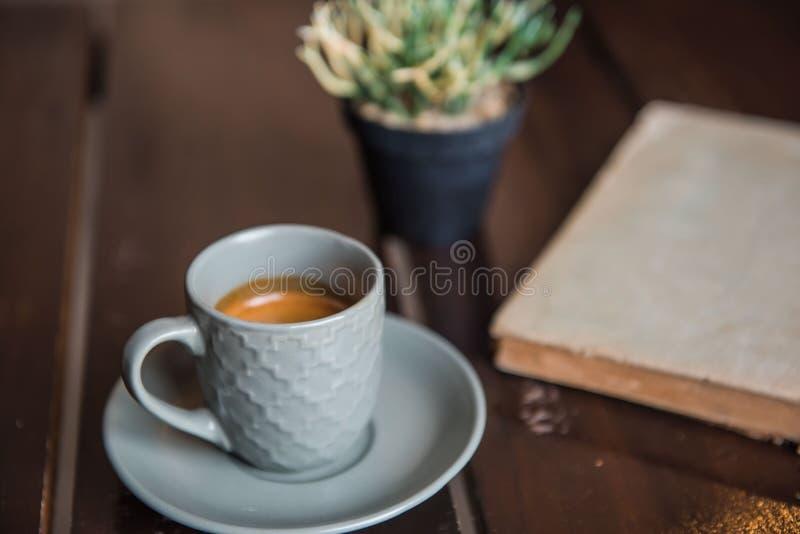 Kupa kaffe på den vita trätabellen och den gamla boken och krukan royaltyfri fotografi