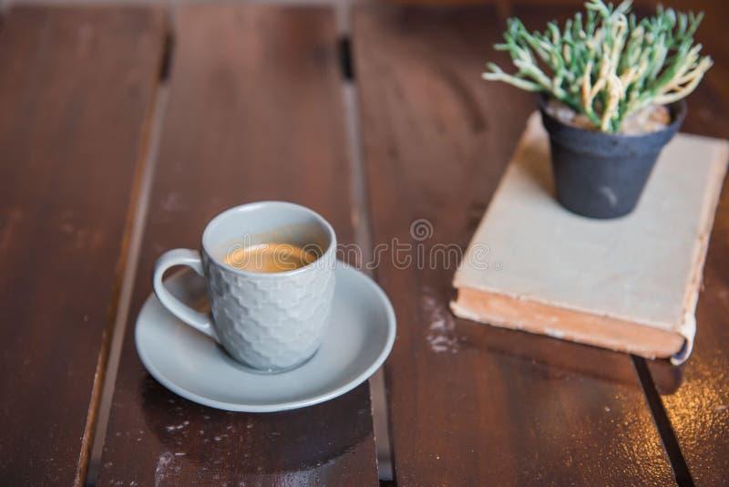 Kupa kaffe på den vita trätabellen och den gamla boken och krukan arkivfoto