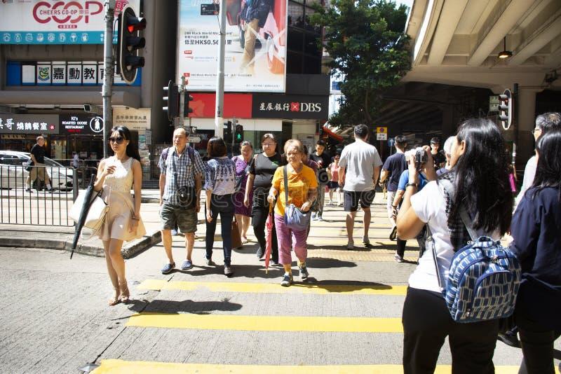 Kupczy drogę z retro tramwajem i chińczykami chodzi skrzyżowanie drogi przy Bladą Chai drogą w Hong Kong, Chiny obrazy stock