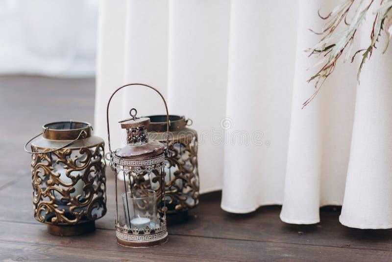 Kupferne Kerzenhalter mit weißen Kerzen als Heiratsdekorationen lizenzfreie stockbilder