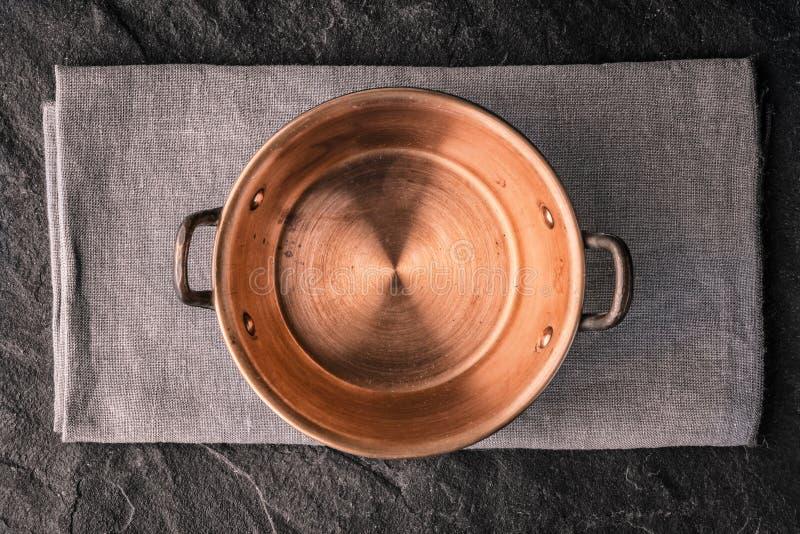 Kupferner Topf auf der dunklen Steintischplatteansicht lizenzfreies stockbild