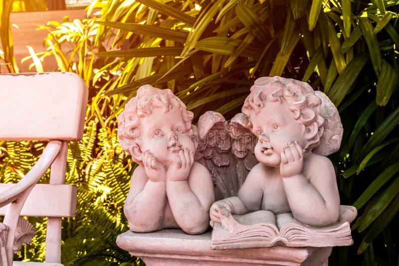 Kupidon- och ängelstaty, pojke och flickastaty i trädgård arkivbild