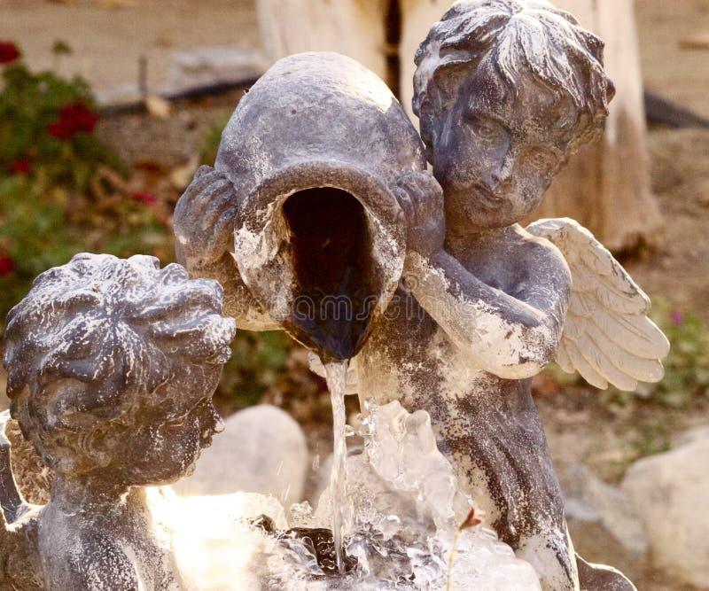 Kupidonstaty med springbrunnen för vattentillbringare royaltyfri fotografi