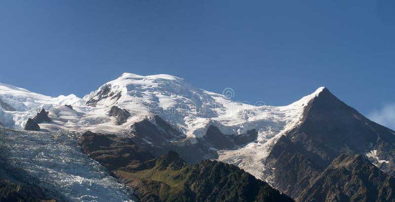 Kupol och Aiguille du Gouter bergmaxima med den Bossons glaciären i de europeiska fjällängarna, ett snöig landskap för sommar arkivbild