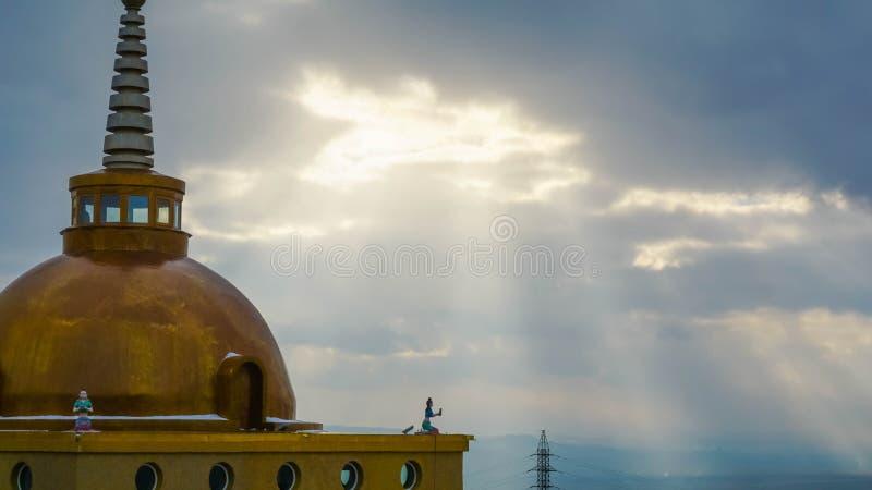 Kupolen av en buddistisk tempel på bakgrunden av solljus som passerar till och med molnen fotografering för bildbyråer