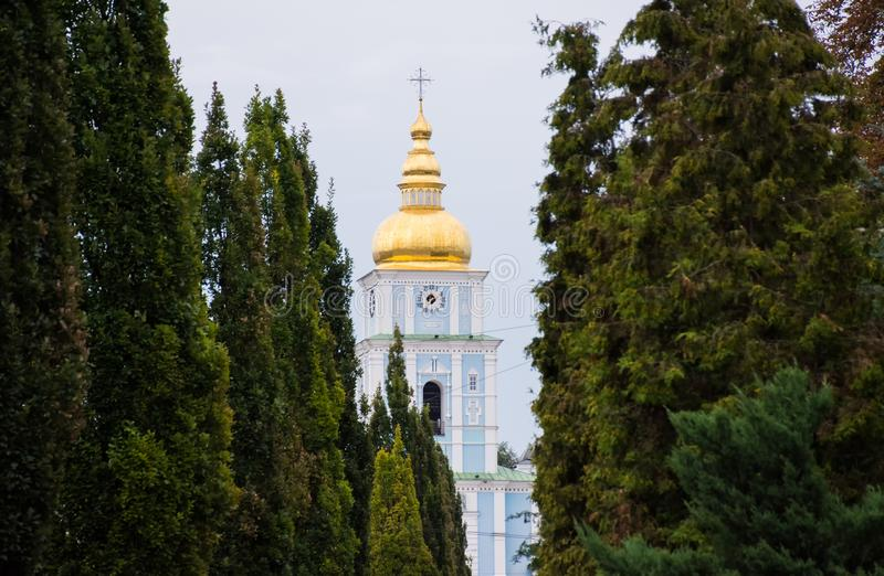 Kupolen med korset och klockan av Christian Church som omges av en korridor av träd - gröna barrträds- arborvitaes royaltyfria foton