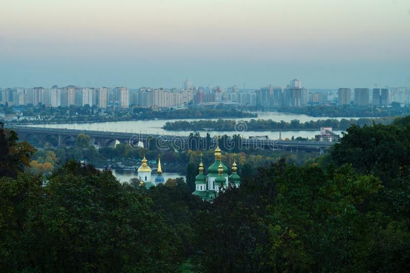 Kupoler av den Vydubychi kloster på bakgrunden av nybyggen i blå skymning, Kiev, Ukraina arkivbild