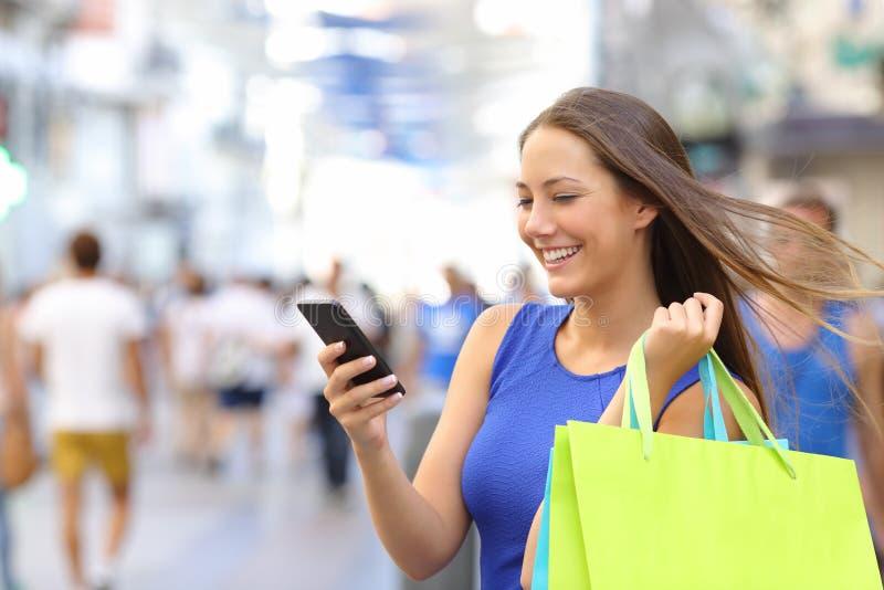 Kupującego zakupy z smartphone w ulicie zdjęcie royalty free