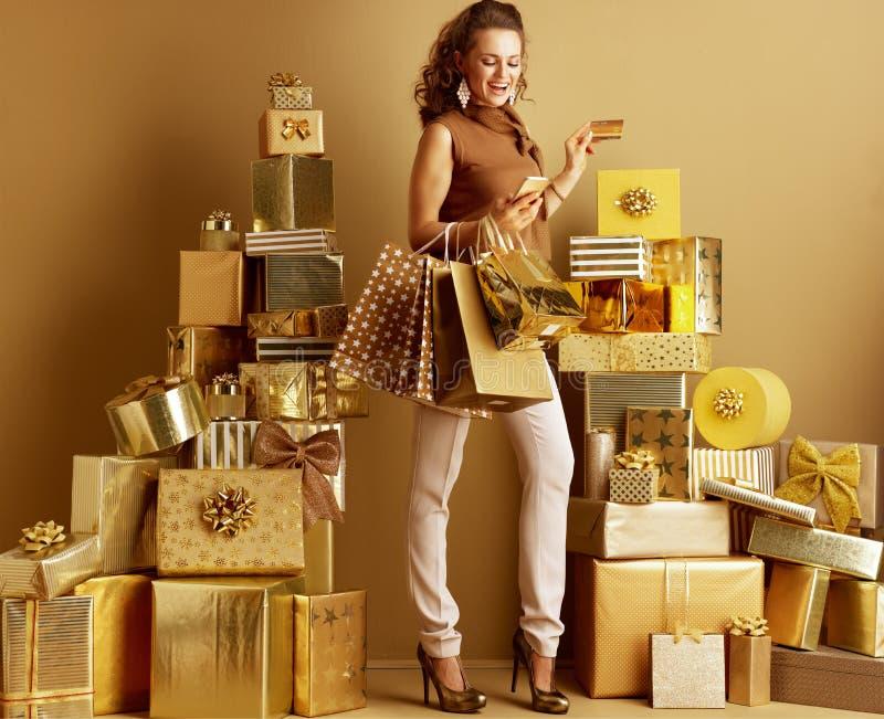 Kupujący kobieta z torbami na zakupy i złotym karty kredytowej patrzeć zdjęcia stock