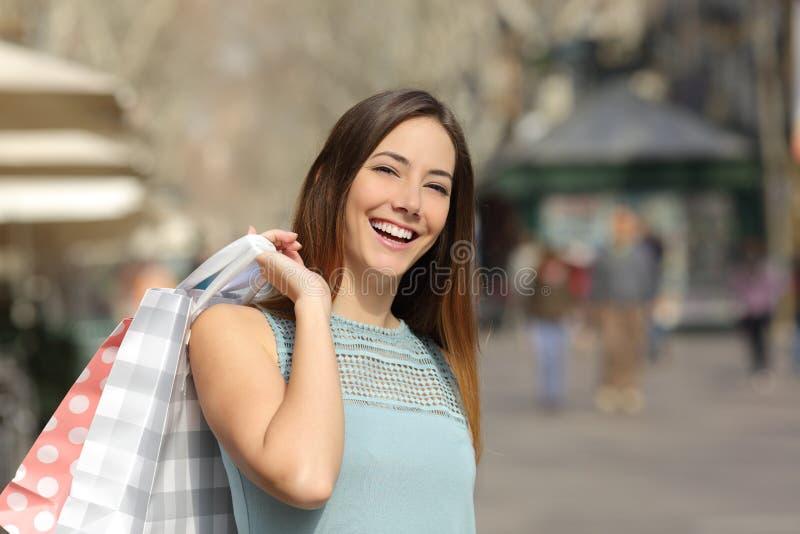 Kupujący kobiety mienia i kupienia torba na zakupy zdjęcia royalty free