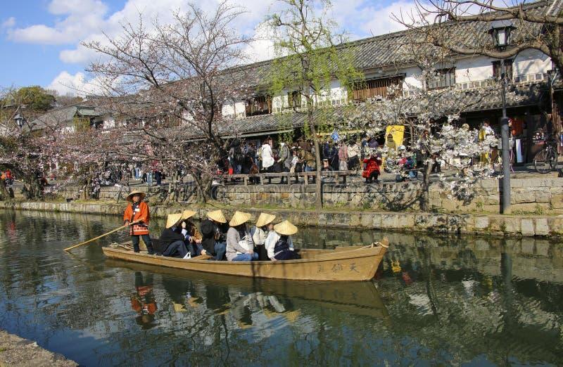 KURASHIKI, JAP?O - 31 DE MAR?O DE 2019: Os turistas est?o apreciando o barco antiquado ao longo do canal de Kurashiki imagem de stock