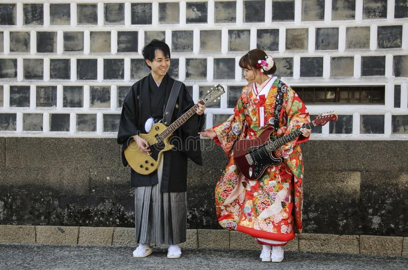 KURASHIKI, JAPAN - MARCH 31, 2019: Young man and a girl in kimono dress imitate playing on electric guitars. Against the background of a traditional wall of a stock image