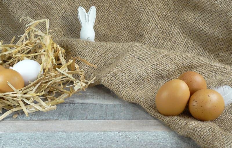 Kurczaków jajka w słomie gniazdują witheaster królika przy burlap nad drewnianym tłem zdjęcie royalty free