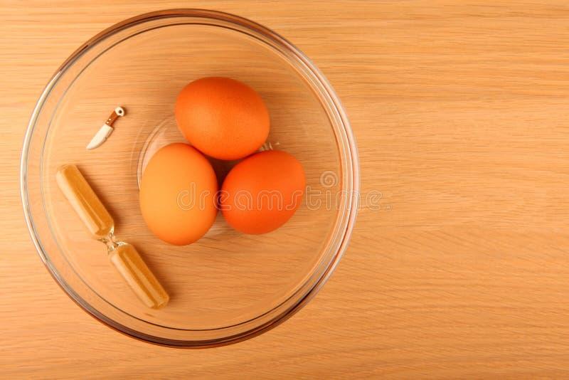 Kurczaków jajek piaska zegaru szklanego talerza zabawki nożowy drewniany stół nikt zdjęcia stock