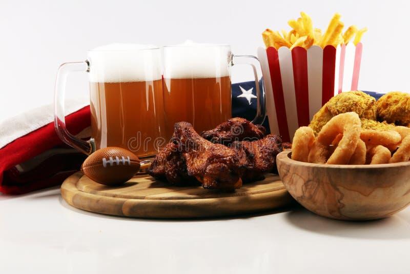 Kurczaków skrzydła, dłoniaki i cebulkowi pierścionki dla futbolu na stole, Wielki dla puchar gry zdjęcia royalty free