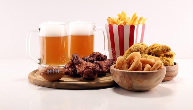 Kurczaków skrzydła, dłoniaki i cebulkowi pierścionki dla futbolu na stole, Wielki dla puchar gry fotografia stock