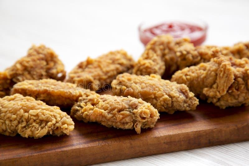 Kurczaków skrzydła na drewnianej desce z czerwonym pieprzowym kumberlandem na białym drewnianym stole, zbliżenie zdjęcia royalty free