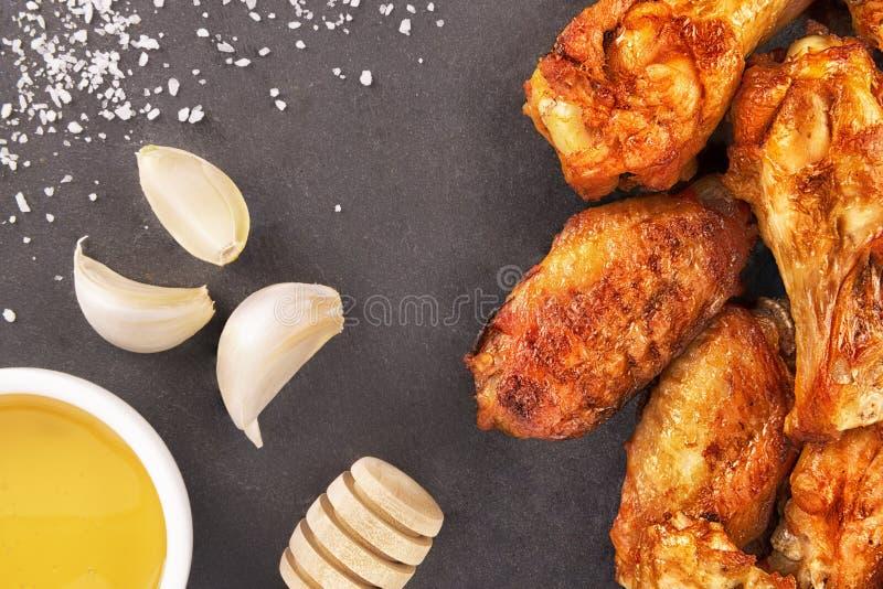 Kurczaków skrzydła z miodem i czosnkiem na czarnym łupku fotografia royalty free