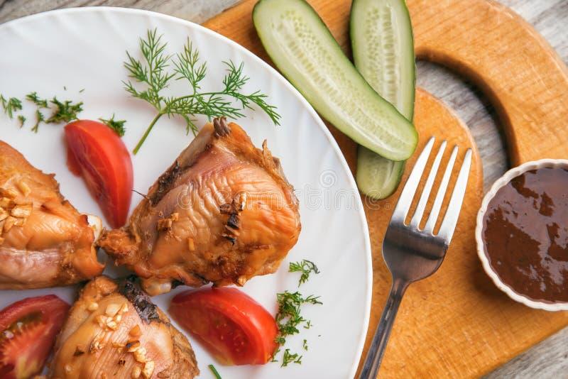Kurczaków uda piec na grillu, pomidor, ogórek i kumberland na drewnianym tle, obrazy royalty free