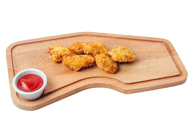 Kurczak bryłek ketchup na tnącej desce odizolowywającej na białym tle obrazy stock