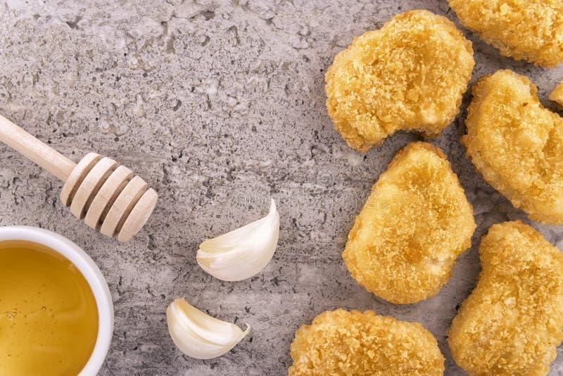 Kurczak bryłki z czosnkiem i miodem na betonowym tekstury tle zdjęcia royalty free