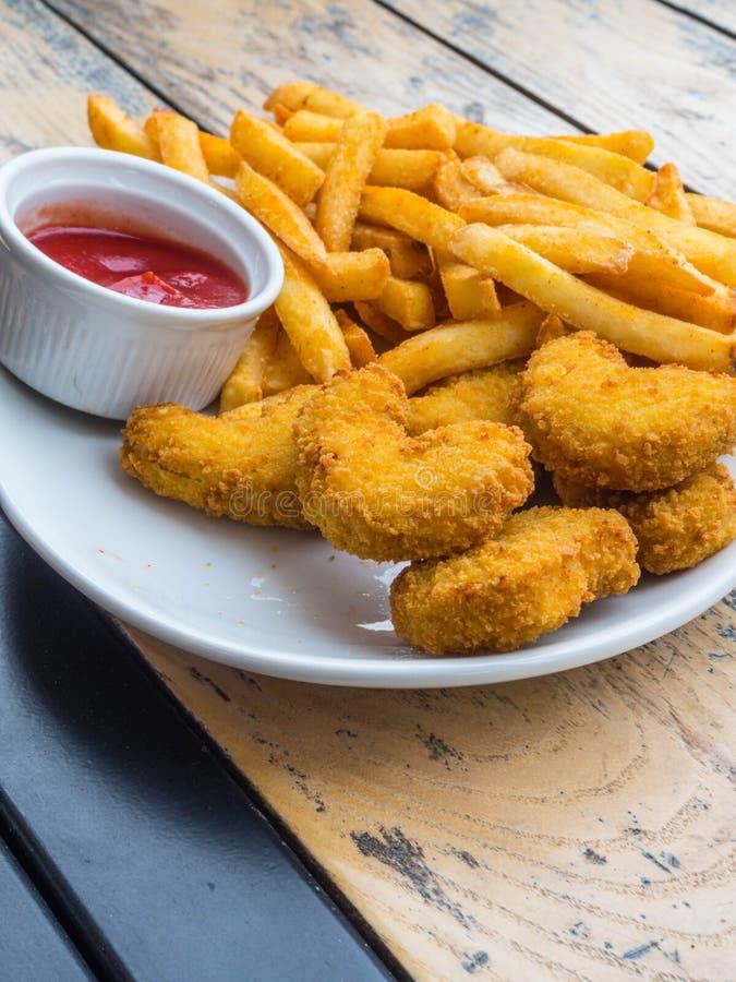 Kurczak bryłki z francuskimi dłoniakami, ketchup na drewnianym tle obrazy stock