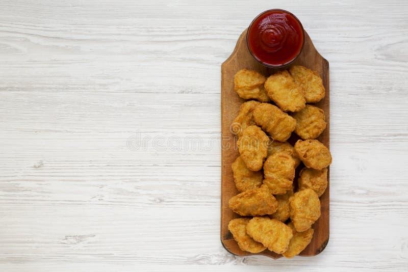 Kurczak bryłki z ketchupem na nieociosanej drewnianej desce na białym drewnianym tle, odgórny widok Mieszkanie nieatutowy, od abo zdjęcie royalty free