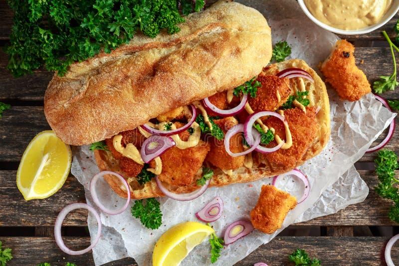 Kurczak kanapka z musztarda kumberlandu i czerwonej cebuli miącym papierem obraz stock