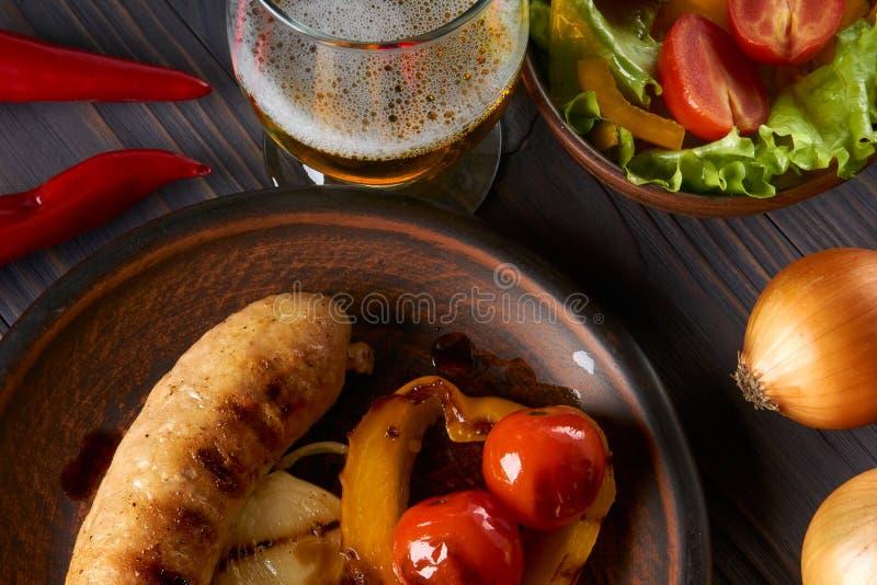 Kurczak kiełbasa z warzywami i lekkim piwem na glina talerzu obrazy stock