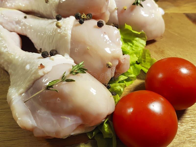 Kurczak nogi surowe, przygotowanie, kucharstwo, pikantność, czarny pieprz, pomidor zdjęcia stock