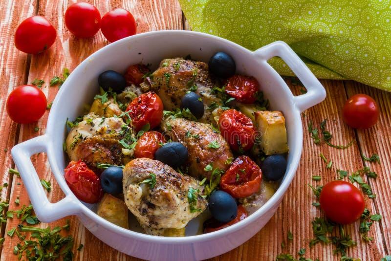 Kurczak nogi z grulami, czereśniowymi pomidorami i czarnymi oliwkami, Biały pieczenia naczynie na drewnianym tle obrazy royalty free