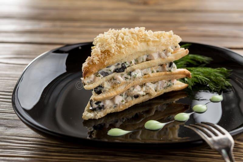 Kurczak, oliwki i pieczarkowy pasztetowy ptysiowy ciasto na drewnianym stole, fotografia stock