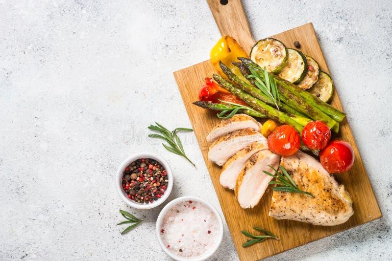 Kurczak pierś piec na grillu z warzywami na drewnianej porcji desce zdjęcia royalty free