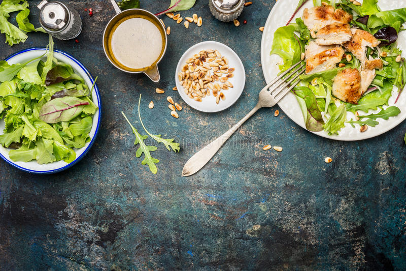 Kurczak sałatka z zielonymi mieszanki sałatki liśćmi, rozwidleniem i opatrunkiem na nieociosanym tle, odgórny widok, granica fotografia stock