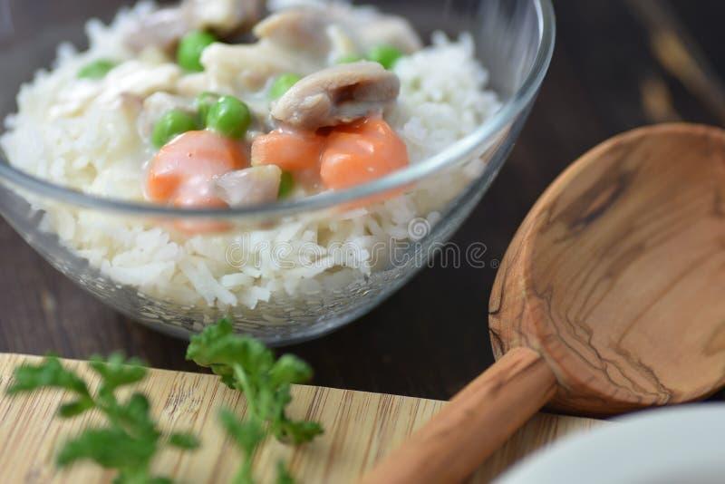 Kurczaka fricassee z zielonym grochem słuzyć z gotowanymi ryż na drewnianym tle zdjęcie stock