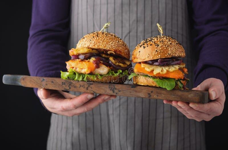 Kurczaka hamburger z ananasem Mężczyzna ` s ręki trzymają tacę z ch zdjęcia royalty free