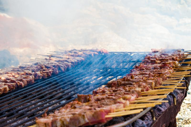 Kurczaka i baranka skewers na prostym, nieociosanym grillu rozkładającym na piasku grecka wyspa, Zamyka w górę smocking mięsa got obrazy stock