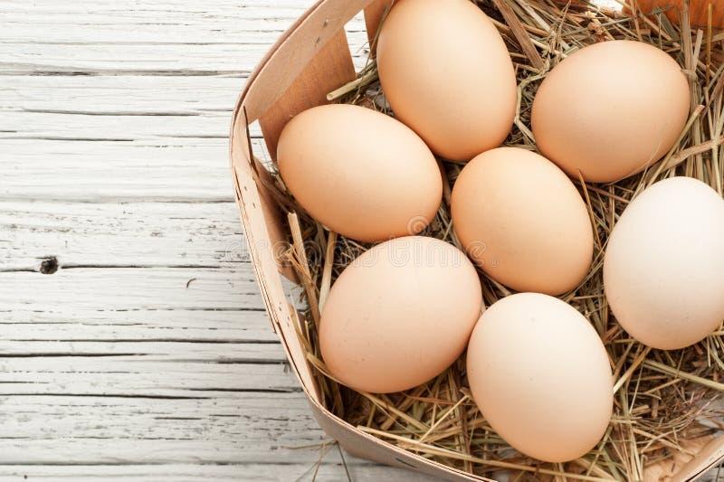 Kurczaka jajko w słomianym gniazdeczku na białym starym drewnianym tle obrazy royalty free