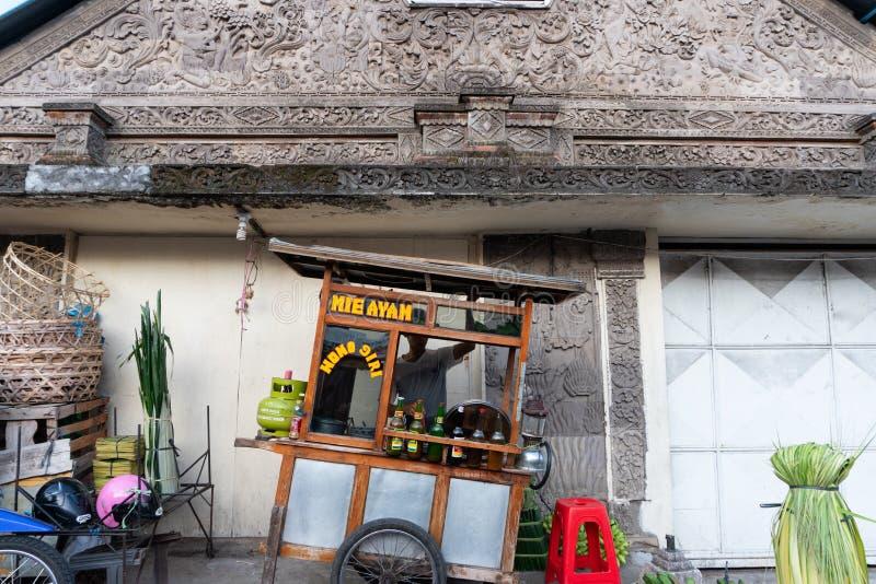 Kurczaka kluski sprzedawca niesie jego fury sprzedawanie na chodniczku w jeden kąty Badung tradycyjny rynek dokąd zdjęcia stock