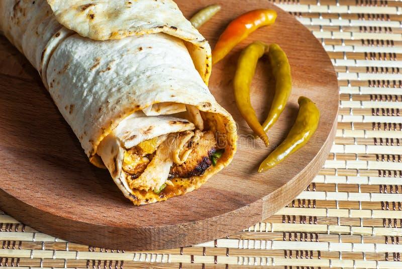 Kurczaka opakunku doner kebap w lavash pita chlebowym durum z cienką zielonego pieprzu zalewą na drewnianym półmisku fotografia stock