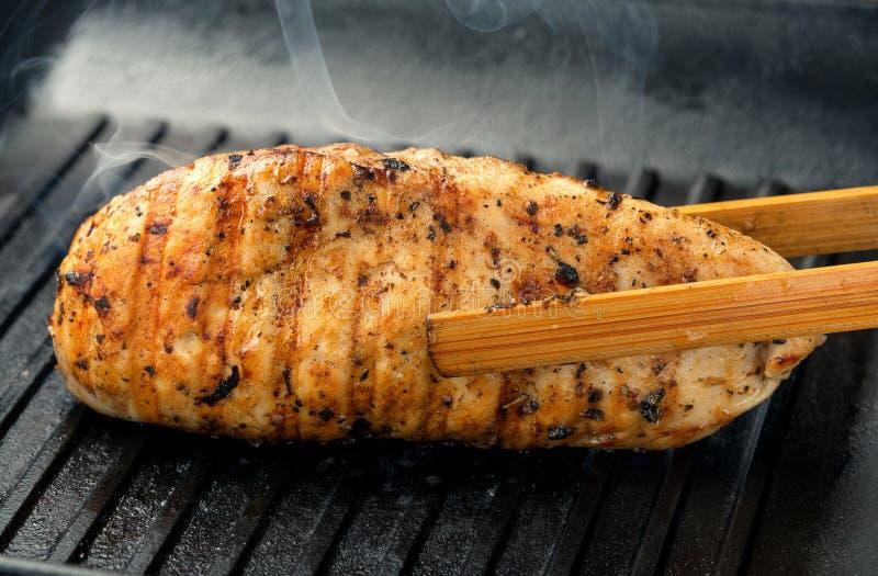 Kurczaka stek piec na grillu na lanym żelaznym rynienka grillu obraz stock