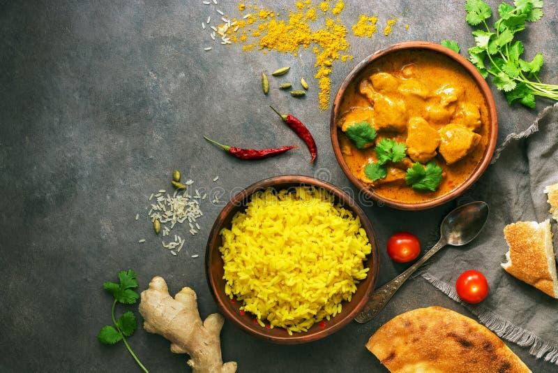 Kurczaka tikka masala korzennego curry'ego mi?sny jedzenie w glinianym pucharu, ry?owego i naan chlebie, Ciemny t?o, odg?rny wido obraz stock