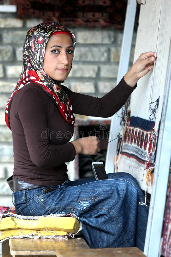 A Kurdish lady making a carpet in Van in eastern Turkey. A Kurdish lady skilfully making a traditional hand make carpet in Van in the far east of Turkey. Each royalty free stock images