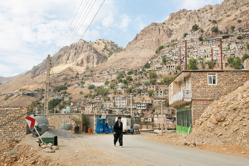 Kurdish man walk on rural road from the old mountaine village in Middle East. HAWRAMAN, IRAN: Kurdish man walk on rural road from the old mountaine village in royalty free stock images