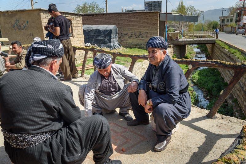Kurdish men playing traditional game with small stones on the streets in Darreh Tafi village near Zarivar lake, Iran royalty free stock image