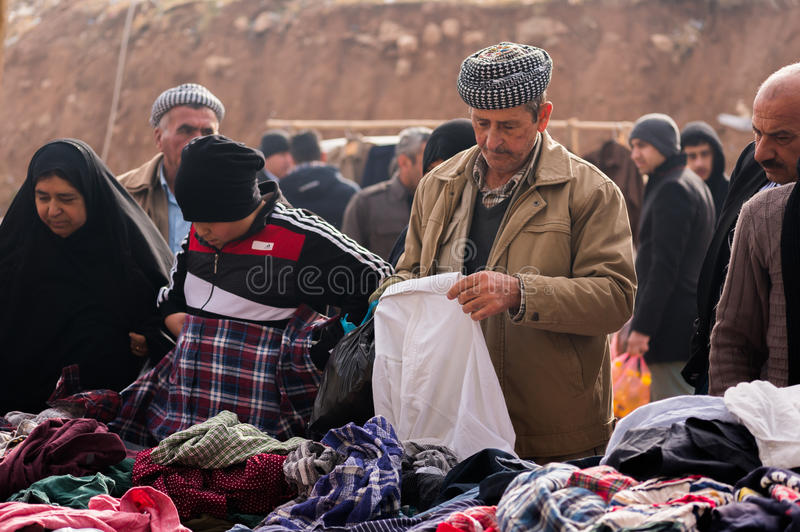 Kurdish People shopping for clothes in Iraq. Kurdish people shopping for winter clothes in a flea market in Iraq wearing traditional costumes stock photo